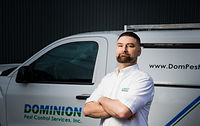 Dominion Pest worker in front of a service truck.