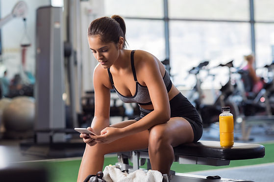 woman-at-gym-using-app-on-smartphone-e15