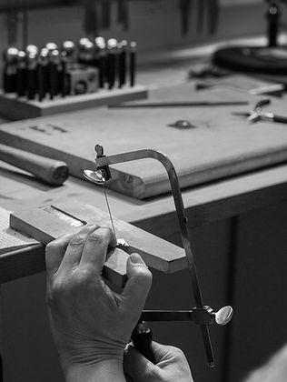 black and white silversmithing studio sawing