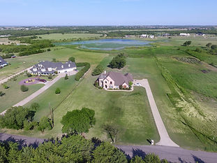 Drone shot of a home with a pond in the background, located in Heath, Texas