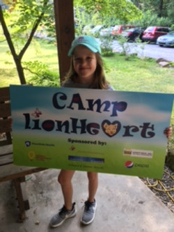 Hannah Holding Camp Sign