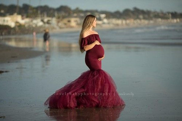 Pregnant Girl on a beach in a wine color tulle dress