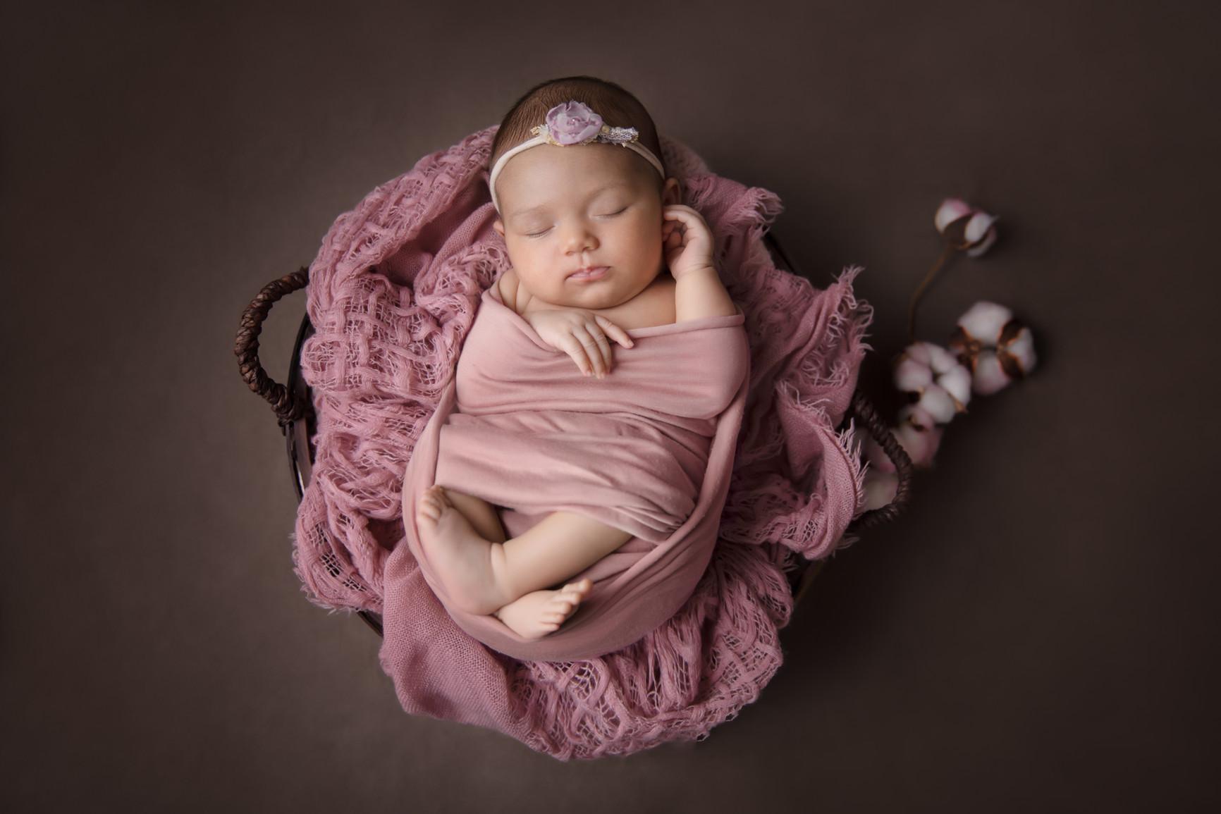 Newborn baby girl in a basket