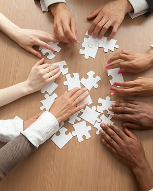 Multiracial team assembling puzzle toget