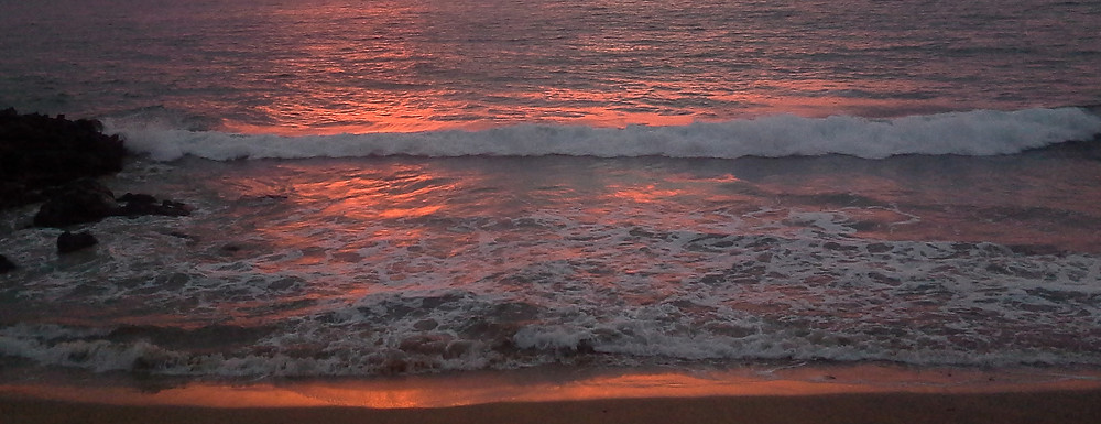 Pink sunset reflected in the surf at the beach
