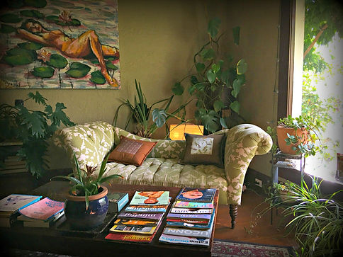 A green waiting room with a swoping sofa, surrounded by many green plants, a large painting of a nude woman among water and lilypads on the wall, and a coffee table covered in magazines. A large window on the right lets in natural light.