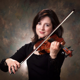 """Violinist Daniela Folker was born in Bucharest, Romania where she began her musical studies at the age of six.  Upon moving to the United States, she furthered her studies completing both a bachelor's and graduate degree in violin performance from Roosevelt University. She is currently Principal Second Violinist for the Elgin Symphony Orchestra and performs regularly with the Joffrey Ballet Orchestra, Chicago Philharmonic, The Ravinia Festival Orchestra, Milwaukee Ballet Orchestra, Lyric Opera of Chicago, Chicago Opera Theater, and Lake Forest Symphony.   Daniela has performed with such classical artists as Luciano Pavaratti and Andrea Bocelli.  She has also performed with such artists as Celine Dion, The Moody Blues, Ray Charles, David Foster, Linda Ronstadt, and has been featured on Late Night with David Letterman and Oprah performing with Natalie Cole. Daniela along with her husband Michael, and son Christopher, regularly perform their educational program entitled """"The Magic of Rhythm"""" which teaches young audiences about the magical joys of music. Daniela is on faculty as the violin instructor at Judson University and  College of DuPage."""