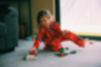 Child in pyjamas playing with toys - jammies in june
