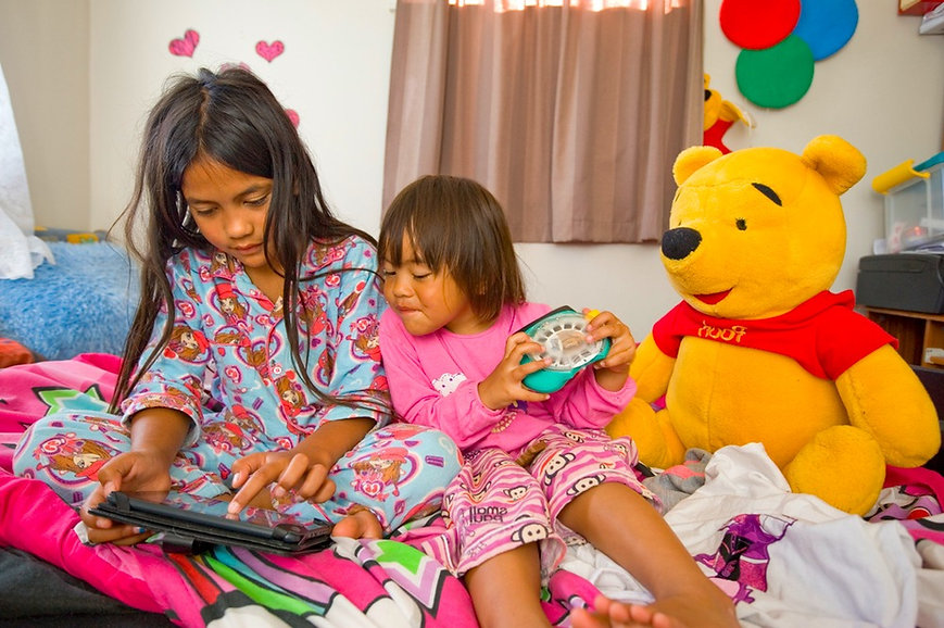 two sisters in pyjamas reading