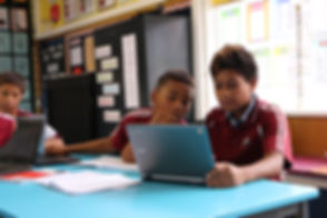children in school learning on a laptop