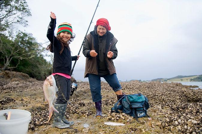 maori grandma and granddaughter fishing together