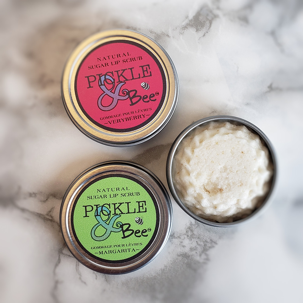 "Pickle & Bee Natural Lip Scrub. One opened container showing creaming product. One pink label ""Very Berry"" sugar lip scrub. One green packaing, Margarita sugar lip scrub."