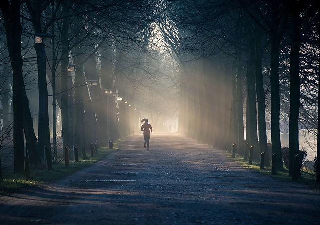 person-running-near-street-between-tall-
