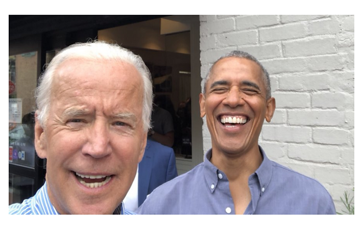 ​Vice President Joe Biden takes a selfie with a laughing President Barack Obama standing in the street.