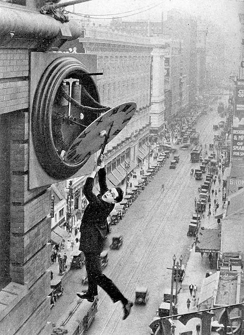 Harold Lloyd hangs from a clock face in the film, Safety Last.