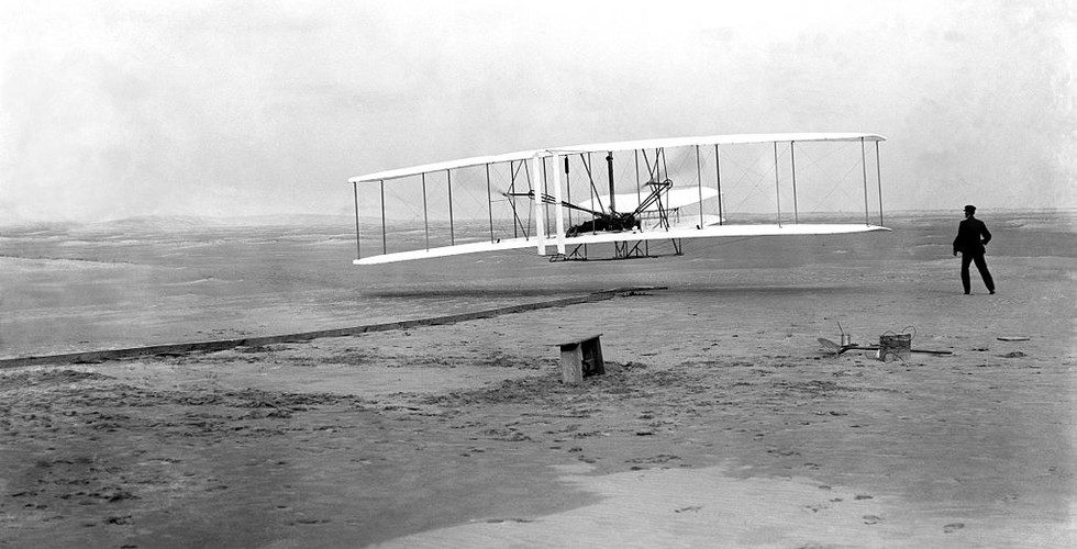 Orville Wright takes to the air in his flying machine on the sands of Kitty Hawk on 17 December, 1903. His borther Wilbur can be seen running beside the machine.