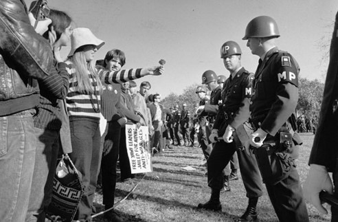 Female peace protester offers a flower to military police at the Pentagon during 1967 anti-Vietnam demonstration.