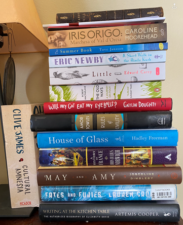 A pile of books on Marcus's bedside table includes the following titles. Cultural Amnesia by Clive James, Iris Origo by Caroline Moorhead, A Short Walk in the Hindu Kush by Eric Newby, Little by Edward Carey, Summer Book by Tove Jansson, House of Glass by Hadley Freeman, Will My Cat Eat My Eyeballs by Caitlin Doughty, May and Amy by Josceline Dimbleby, Rules and Civility by Amor Towles, Fates and Furies by Lauren Goff, The Old Ways by Robert MacFarlane, and Writing at the Kitchen Table by Artemis Cooper.