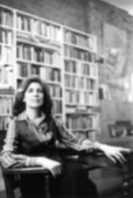 A black and whte photograph of Susan Sontag. She is seated before a high bookcase in her home in 1979. She stares ito the camera lens, a slight smile playing on her lips.