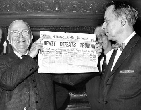 A jubilant President Harry S. Truman holds aloft a copy of the Chicago Daily Tribune. The headline reads Dewey defeats Truman.