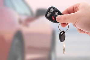 Person holding car keys out