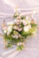 Pink cherry blossom, ranunculus, and hellebore wedding bouquet made by Washington wedding florist.