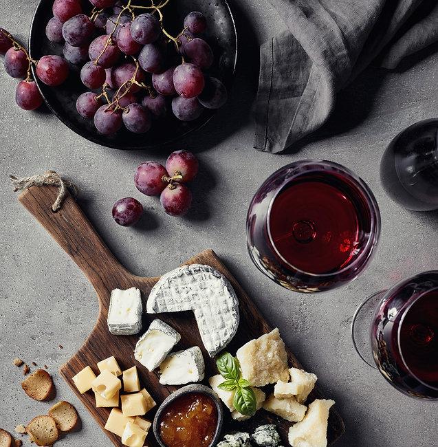 Copo de vinho tinto, uvas e queijo