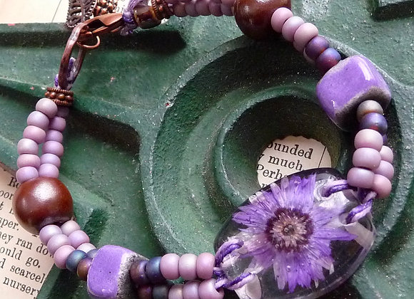Purple beaded bracelet with floral lucite focal bead.
