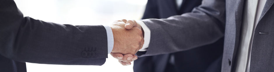 This photograph is a close-up of two businessman shaking hands.
