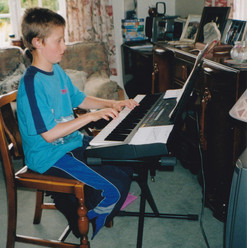 A young Matthew practicing on a keyboard