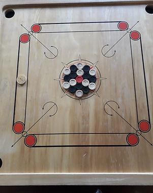 Mariecultive-locationdejeuxgeants-Carrom-Ce jeu est aussi appelé le billard indien est un jeu de stratégie qui demande aussi de la dextérité pour mettre un maximum de pions de sa couleur dans les trous des coins.