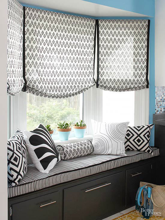 Black banding on relaxed roman shades over a window seat with designer throw pillows