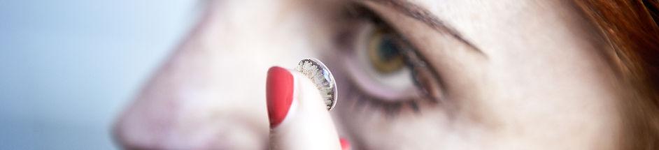 young woman putting contact in eye.jpg