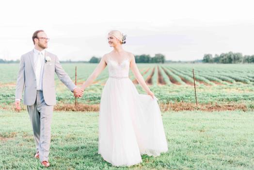 Couple holding hand in vine yard, rural louisiana wedding