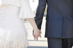 Couple qui marche main dans la main pour entrer dans la salle de réception .