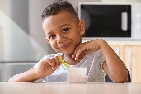 Cute African American boy eating yogurt