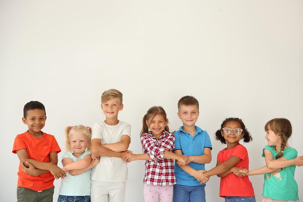 Little children holding hands on light b
