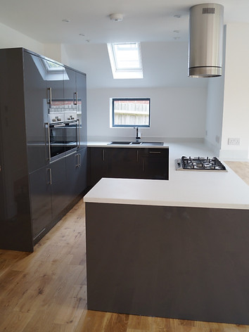 Modern Kitchen With Corian Worktops And Oak Flooring