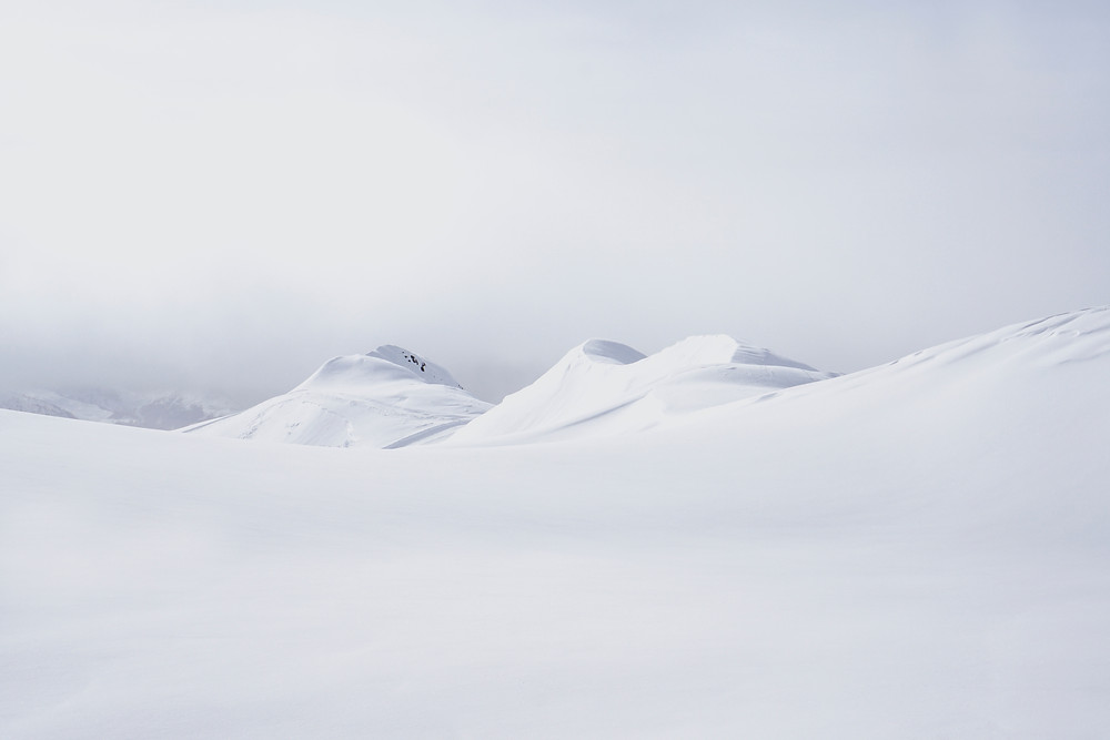Snow covered mountains with a foggy mist in the background.