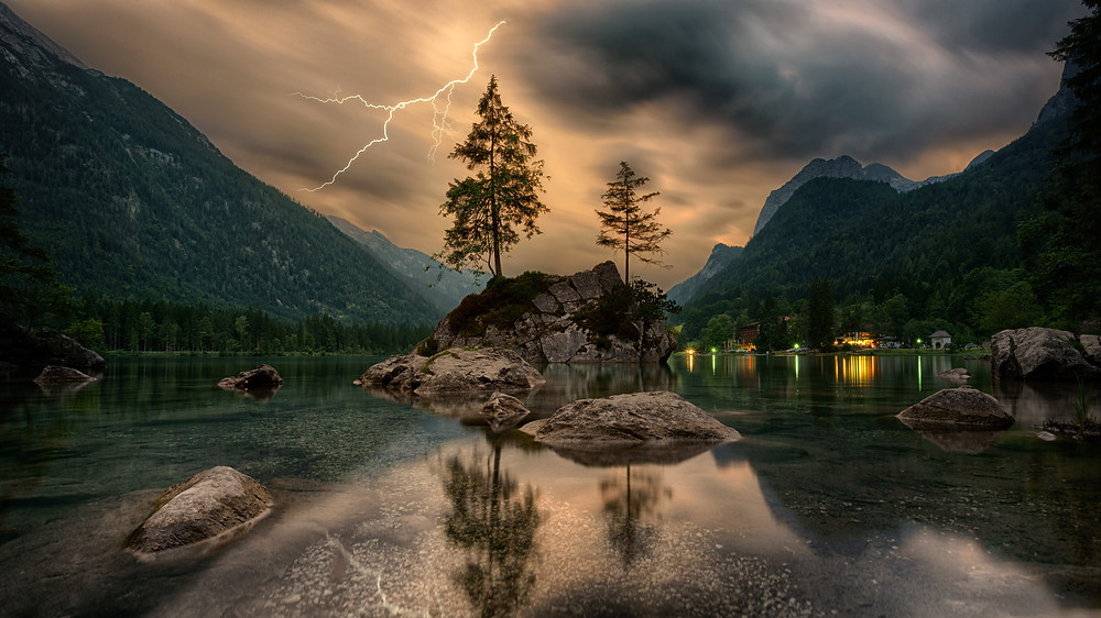 Mountains surrounding a lake with rocky islands with pine trees in the middle. Lightning flashes in the background.