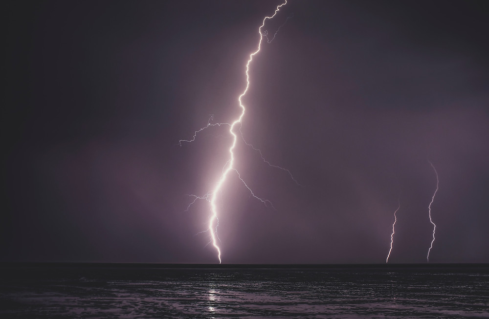 Three bolts of lightning streaking from the sky to the sea