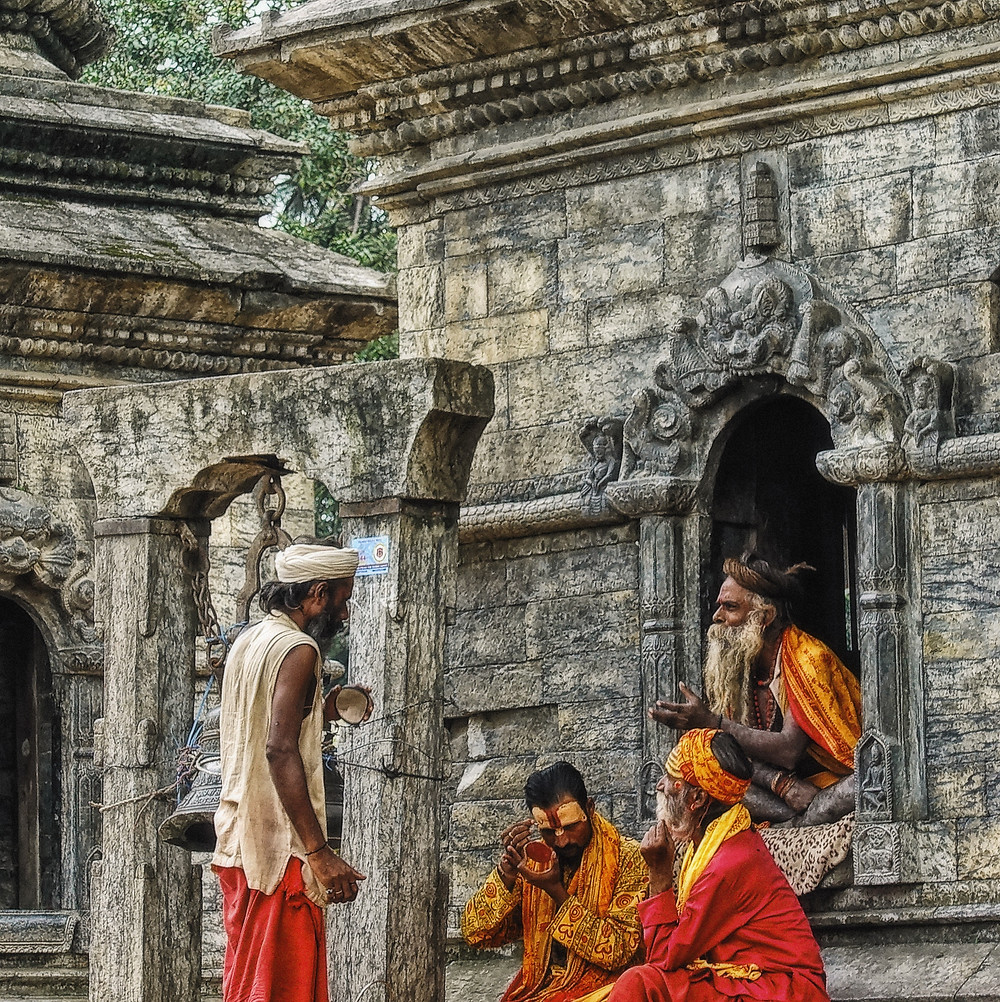 Holy men in bright red and yellow clothing speaking with each other.