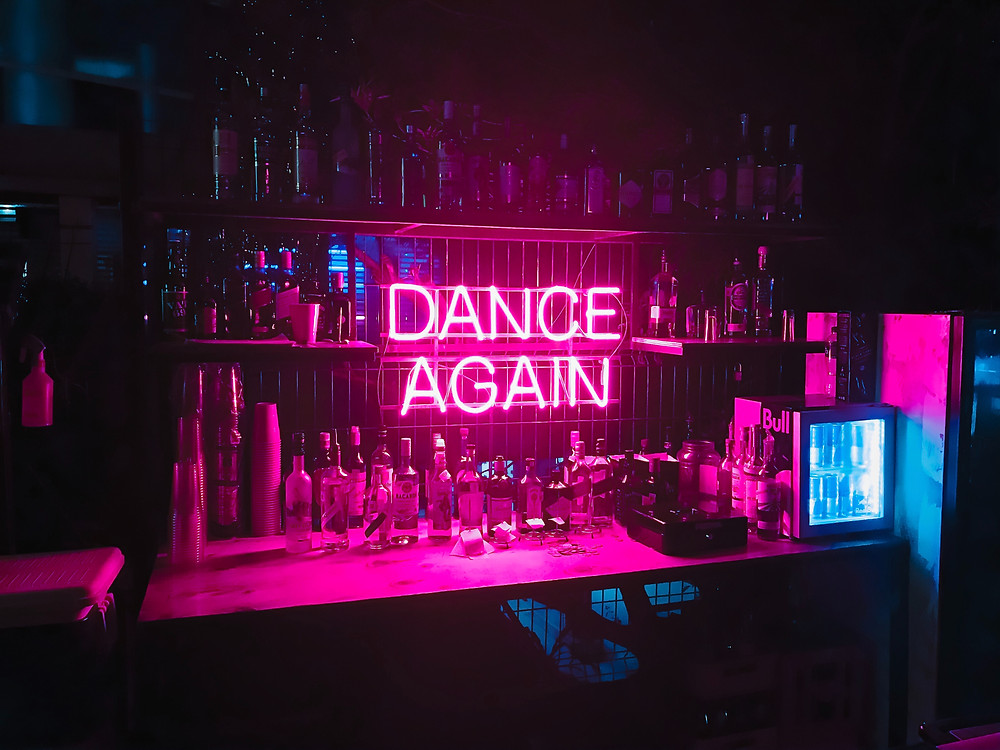 "Bar with alcohol bottles all around, lit up by a neon sign that says ""Dance Again"""