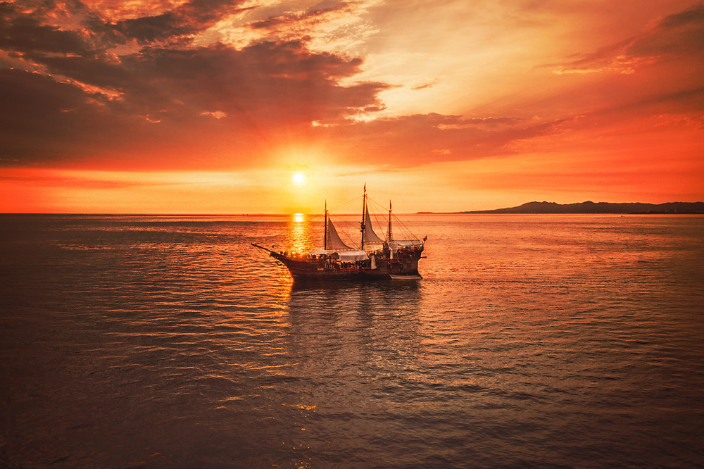 Ship on the water with an orange sunset