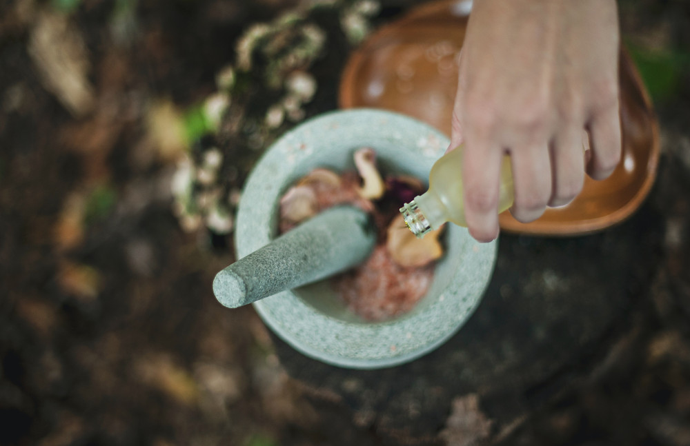 Herbalist mixing herbs and essential oils with a mortar and pestle