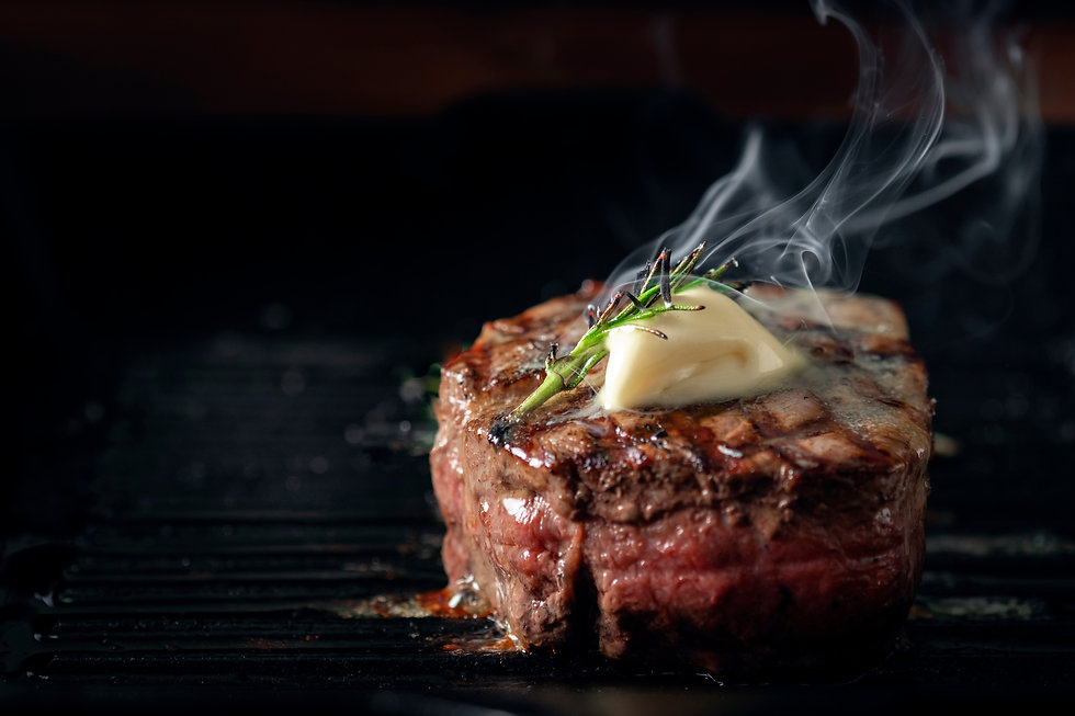 A steaming beef tenderloin steak is grilled in a grill pan with the text copy space. The c