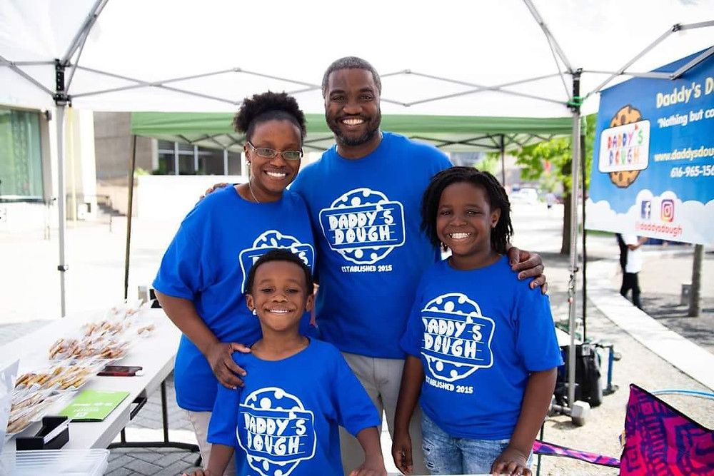 A family that works together is a powerful one. MarcQus(top-right), his wife Tawanna(top-left) and their two beautiful kids Malcolm & Mariah selling Daddy's Dough at the Farmer's Market at GVSU's Allendale Campus