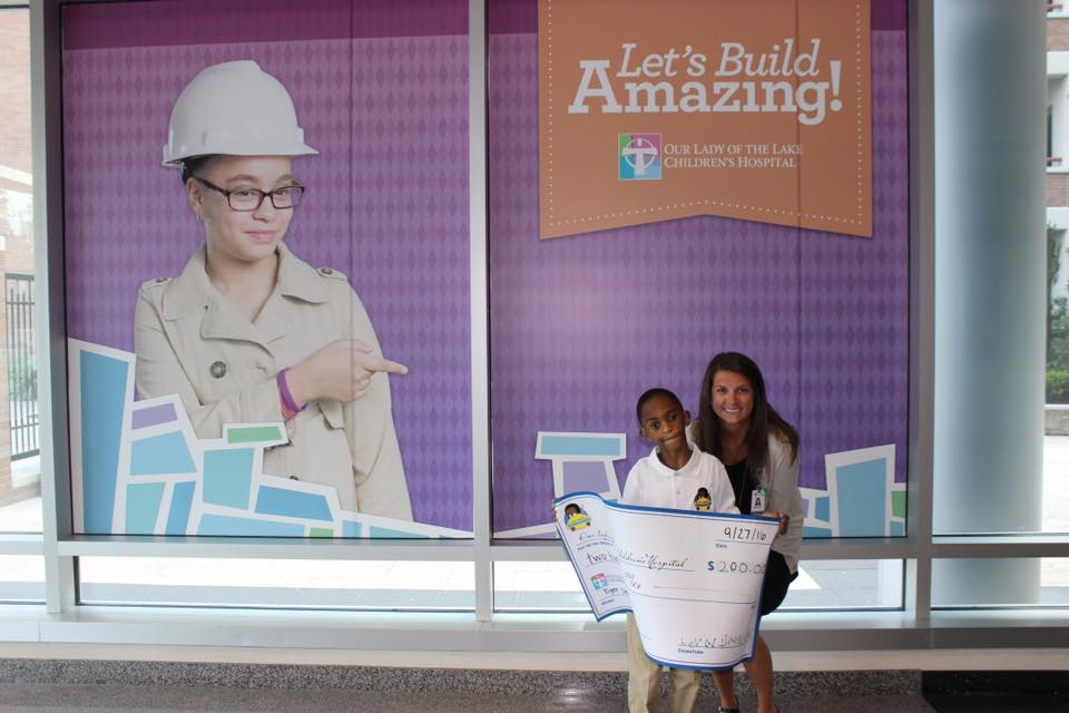 "Leroy III signing his first check to ""Our Lady Of The Lake Children's Hospital, Baton Rouge"" from so"
