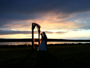 Bride and groom kissing with a beautiful sunset after their wedding