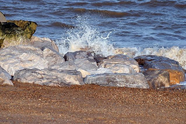 Waves crash into large rocks at the beach
